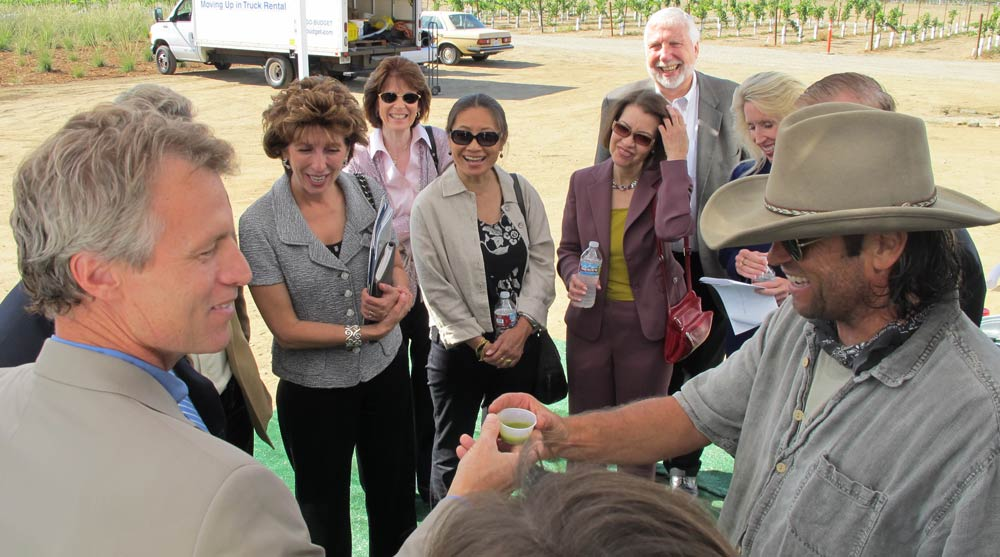 Thom Curry (right) offers fresh olive oil to campus officials.